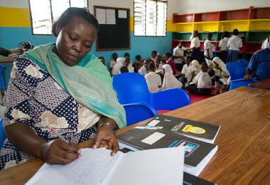 生徒が自宅で本を読むために貸し出しを手伝う先生