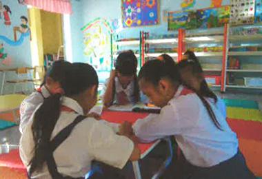 図書室で一緒に読書をする生徒たち